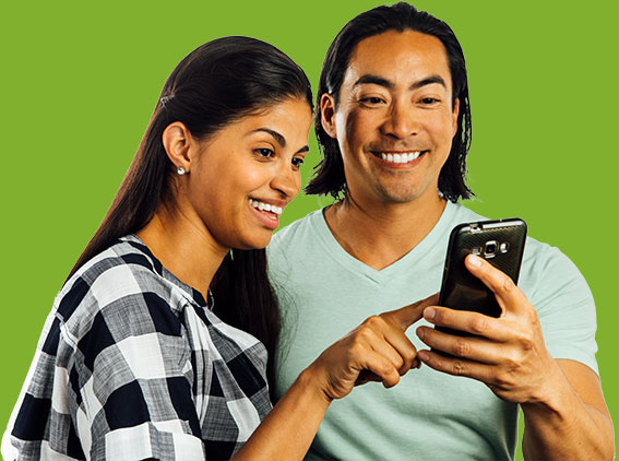 smiling couple looking at smart phone