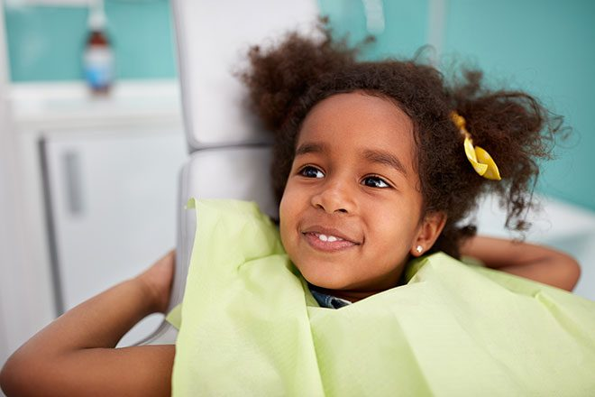 girl smiling in dentist chair