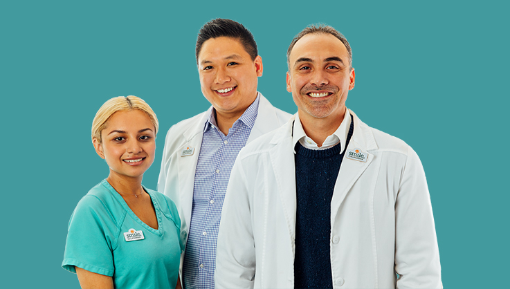 smiling dentists and dental assistant