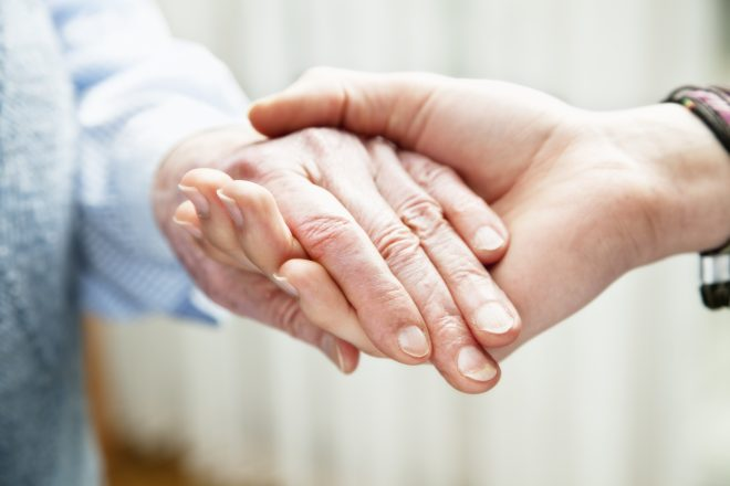 young woman holding hand of a very old woman